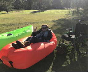 Image description: Anita relaxing in an outdoor blow up lounge